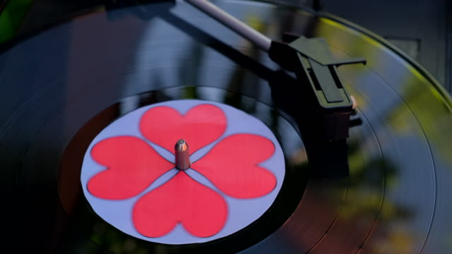 Black vinyl record with red hearts spinning on DJ turntable.  Antiquarian record player. Needle playing record album Popular music equipment for 60s, 70s, 80s, 90s. Love concept Close up, Macro