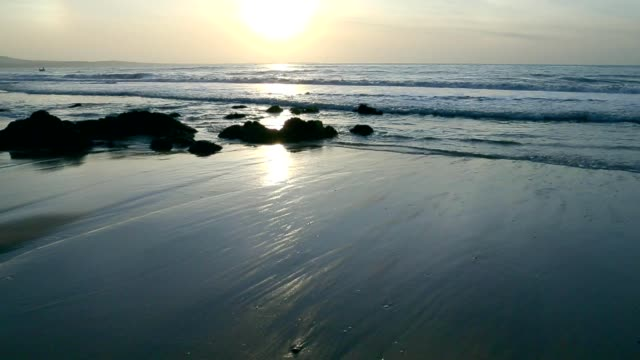 Black wet sand at morning near seashore. video
