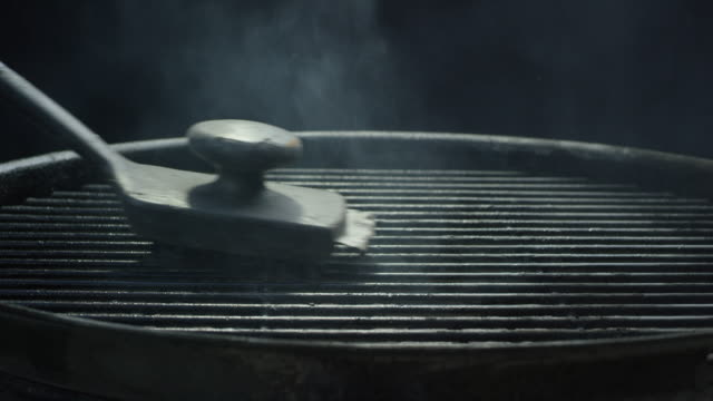 a black wire brush cleans the metal grate of an outdoor barbecue grill - alla griglia video stock e b–roll