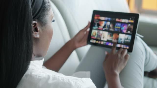 vídeos y material grabado en eventos de stock de mujer negra navegando internet para películas de tv en la tableta - descargar internet