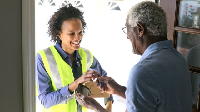 Black Woman Delivers package to customer A young black woman delivers a package to a senior black man post structure stock videos & royalty-free footage