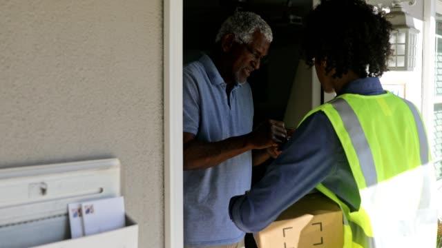 黑人婦女將包裹交付給客戶 - postal worker 個影片檔及 b 捲影像
