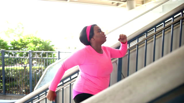 Black woman exercising in city, power walking up stairs video