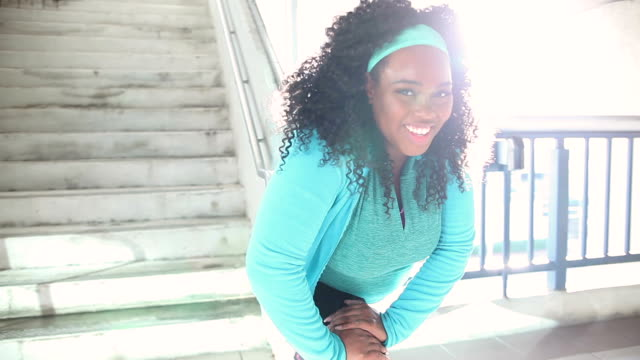 Black woman exercising in city, stretching video