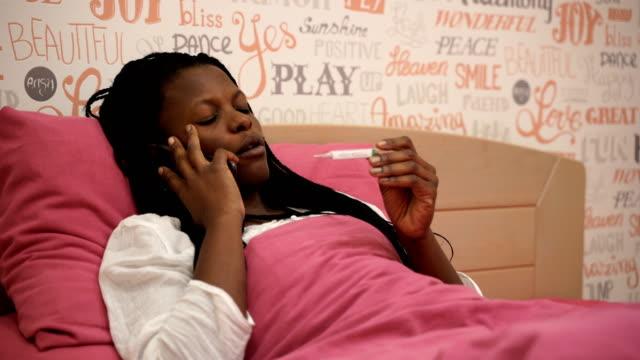 vídeos de stock e filmes b-roll de black woman feeling sick and seasonal flu symptoms,calling a doctor for advice - doença