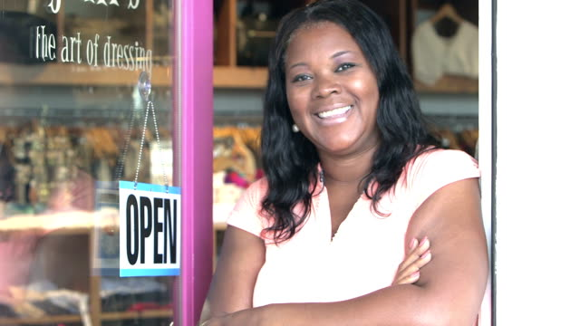 black woman hanging open sign on door of clothing store - open sign stock videos & royalty-free footage