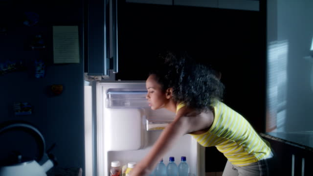 Black Woman Looking into Fridge For Midnight Snack African american woman doing midnight snack at home. She eats a sandwich and looks for food into the refrigerator at night. fridge stock videos & royalty-free footage