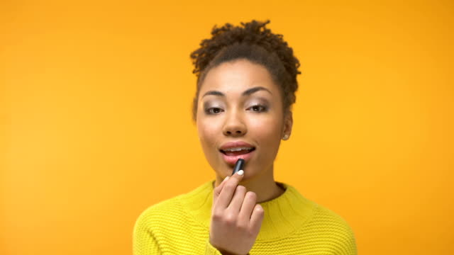 Black woman putting lipstick and sending air kiss to camera, enjoying outlook Black woman putting lipstick and sending air kiss to camera, enjoying outlook lipstick stock videos & royalty-free footage