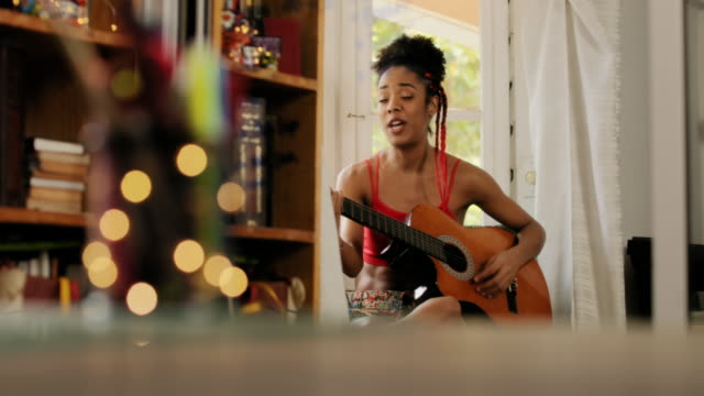 Black Woman Singing And Playing Guitar At Home Black girl lying on couch and singing song, young african american woman relaxing. Happy latina sitting on sofa and playing guitar. Hispanic people and lifestyle. Music, leisure and relaxation at home guitar stock videos & royalty-free footage