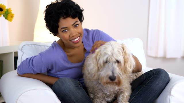 Negro Mujer sonriendo e interactivo wheaten terrier - vídeo