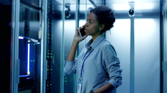 black woman speaking on phone in server room - call center стоковые видео и кадры b-roll