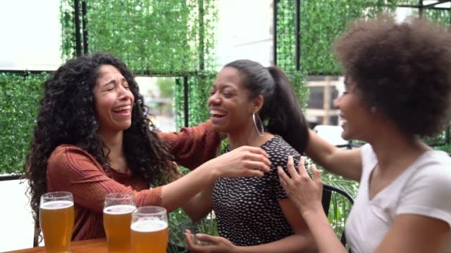 vídeos de stock, filmes e b-roll de mulher preta que diz a seus amigos boas notícias quando abraçam e brindam com cerveja - parabenizando
