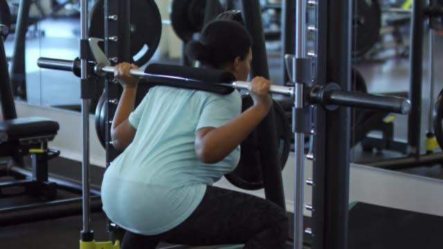 vídeos de stock e filmes b-roll de black woman training with smith machine - agachar se