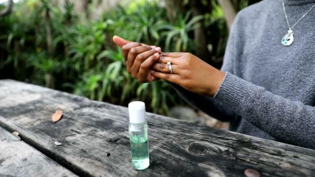 vídeos y material grabado en eventos de stock de mujer negra usando desinfectante de manos para lavarse las manos - hand sanitizer