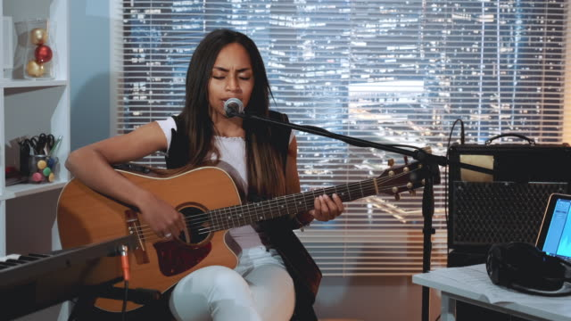 black woman vocalist recording a song and playing guitar in home studio - cantante video stock e b–roll
