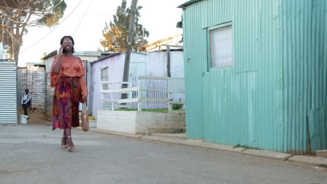 Black woman walking to work and talking on her mobile phone Well-dressed black woman walks through the township on her way to work while she talks on her mobile phone - Kayamandi, Cape Town south africa stock videos & royalty-free footage