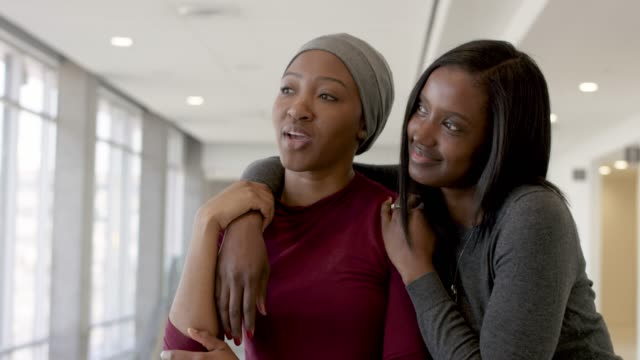 Black Woman With Cancer Spending Time With Her Sister A young adult woman with cancer is sitting inside a hospital interacting with her best friend and sister. sister stock videos & royalty-free footage