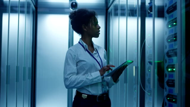 black woman with tablet working in server room - supporto tecnico video stock e b–roll