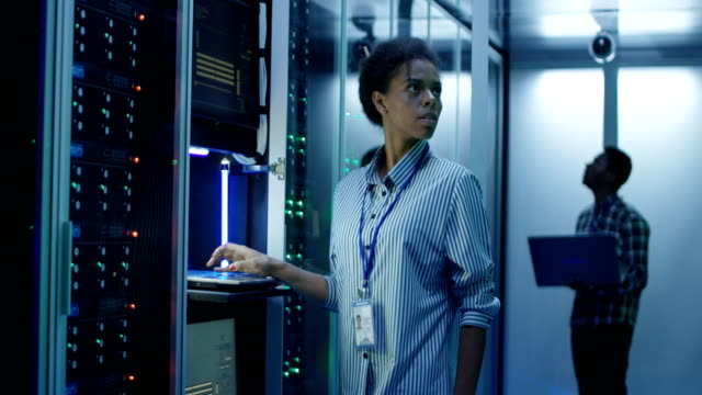 Black woman working on computer in data center video