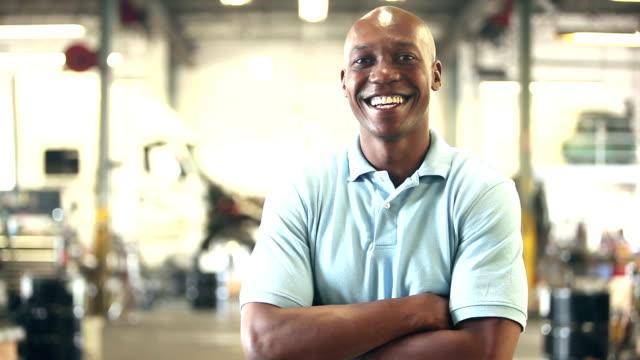 vídeos de stock e filmes b-roll de black worker in trucking industry, smiling at camera - homem casual standing sorrir