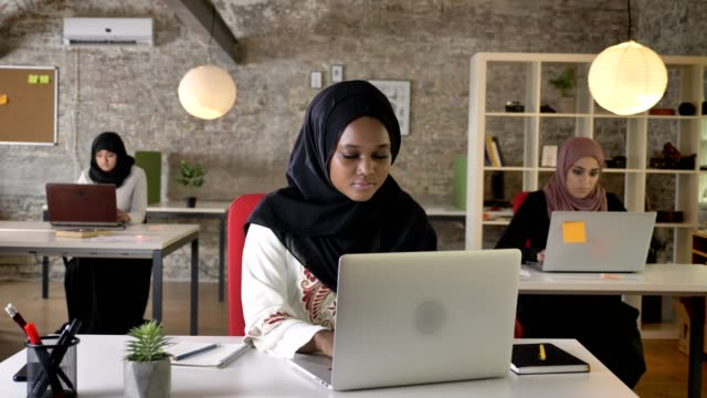 black young muslim woman in hijab typing on laptop and smiling in camera, three beautiful muslim womens working in office - nigeria video stock e b–roll