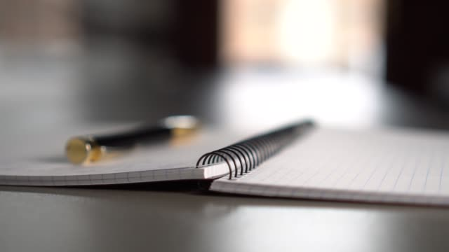 A black-gold pen lies on an open notebook on a gray table in front of a window.