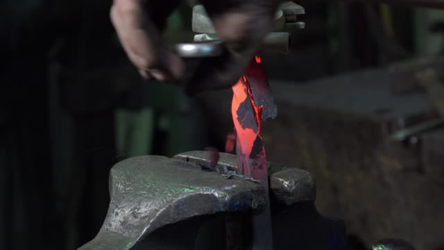 blacksmith artist in his workshop forging a square iron to twist it wrought iron stock videos & royalty-free footage