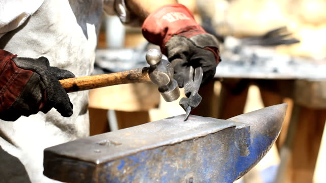 Blacksmith at work Blacksmith hit with a hammer by a hot metal on the anvil wrought iron stock videos & royalty-free footage