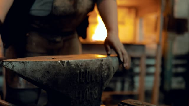 Blacksmith cleans the anvil. Blacksmith shakes off the workplace. Close-up Blacksmith cleans the anvil. Blacksmith shakes off the workplace. Close-up anvil stock videos & royalty-free footage