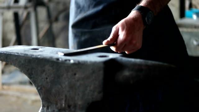 Blacksmith forging a iron bar on anvil block