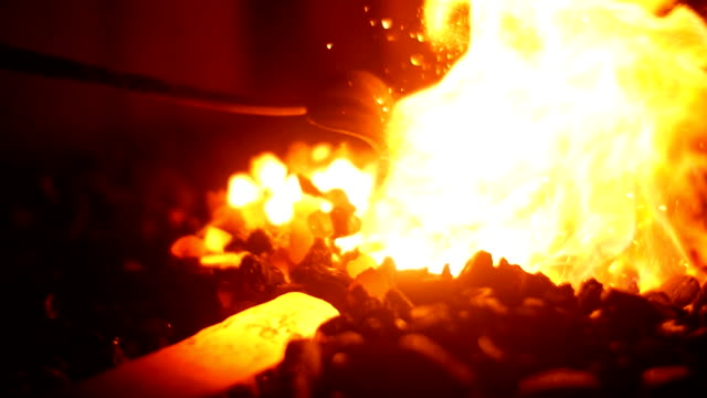 A Blacksmith Forging a Sword in his Workshop at his Forge inside Burning Coals and Flames in Slow Motion video