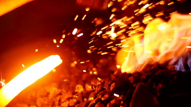 A Blacksmith Forging a Sword in his Workshop at his Forge inside Burning Coals and Flames in Slow Motion A Blacksmith Forging a Sword in his Workshop at his Forge inside Burning Coals and Flames in Slow Motion. All actions are accurate. The Forge is completely authentic. (100fps) anvil stock videos & royalty-free footage