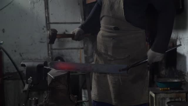 vídeos y material grabado en eventos de stock de herrero forjando hierro caliente en un taller - aleación