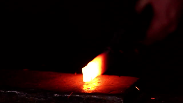 Blacksmith forging hot iron, sparks, slow motion, slider move, closeup video