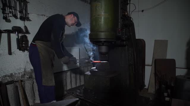 vídeos y material grabado en eventos de stock de herrero forjando hierro caliente rojo bajo enorme prensa - aleación