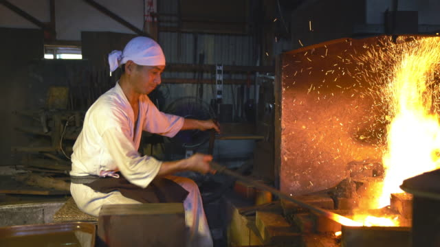 Blacksmith furiously pumping the bellows on his furnace video
