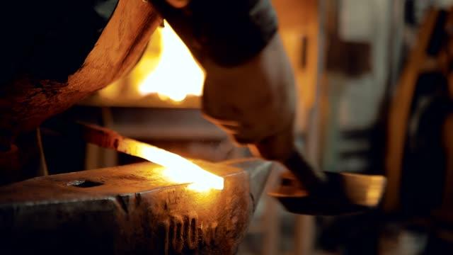 il fabbro prende il metallo dalla fornace e lo bussa con un martello. primo piano - fabbro ferraio video stock e b–roll