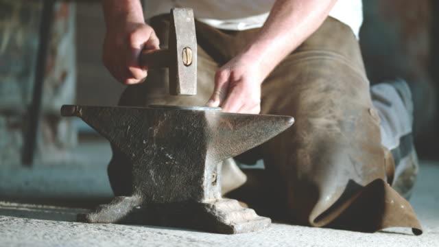 SLO MO Blacksmith hammering a horseshoe
