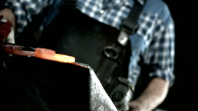 stockvideo's en b-roll-footage met hd slow motion: blacksmith hammering a horseshoe - smid