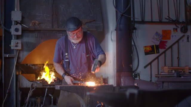 Blacksmith hits hot metal on anvil in slow motion video