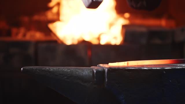 fabbro che colpisce la barra di metallo caldo con un martello massiccio sull'incudine al rallentatore. - fabbro ferraio video stock e b–roll