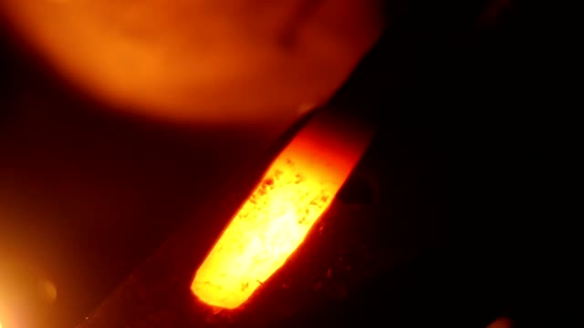 Blacksmith Hitting Hot Metal with a Massive Hammer on an Anvil in Slow Motion video