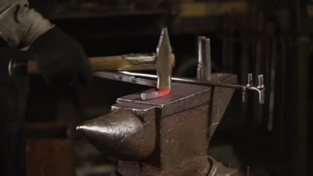 Blacksmith is beating over warmed metal billet on an anvil in forge Forger is hitting red hot steel detail. He is using large heavy sledgehammer, curving billet , lying on an incus. handbook stock videos & royalty-free footage