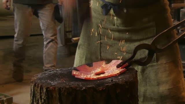 il fabbro sta usando il martello per forgiare il metallo. il fabbro forgia manualmente il metallo fuso sull'incudine in fucina con fuochi d'artificio a scintilla. primo tempo - fabbro ferraio video stock e b–roll