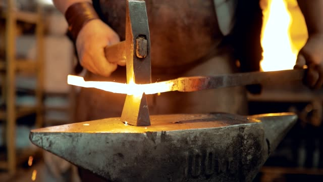 Blacksmith knocks the hammer on the iron on the anvil. Blacksmith's workplace. Close-up Blacksmith knocks the hammer on the iron on the anvil. Blacksmith's workplace. Close-up iron metal stock videos & royalty-free footage