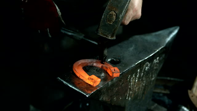 HD: Blacksmith Making Holes In A Horseshoe video