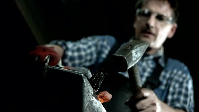 HD: Blacksmith Making Holes In A Horseshoe HD1080p: LOW-ANGLE shot of a blacksmith making nail holes in a horseshoe. Changing focus from a horseshoe to a blacksmith's face. wrought iron stock videos & royalty-free footage
