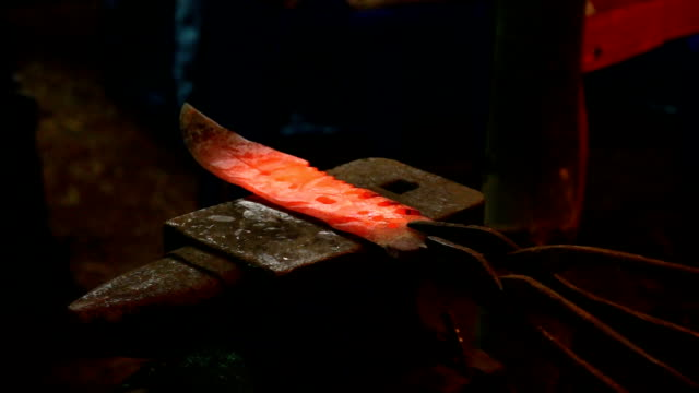 blacksmith manually forging hot metal knife on anvil in traditional video