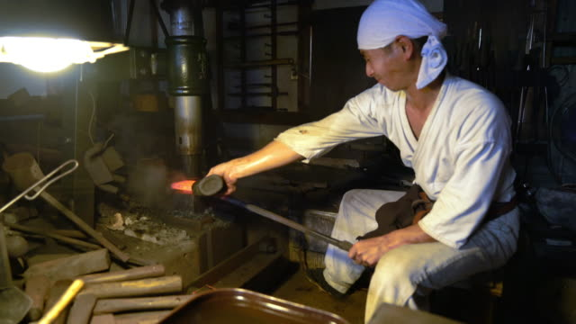 Blacksmith moulding a block of metal Traditional Japanese blacksmith shaping a block of metal using a hammer press. Okayama, Japan. October 2016 blacksmith stock videos & royalty-free footage