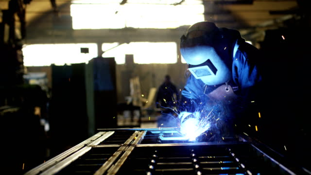 blacksmith or welder,with its grinding smooths steel and iron,in extreme slow motion,to make the surface smooth.the grinding wheel contact with the iron causes sparks. - работник физического труда стоковые видео и кадры b-roll
